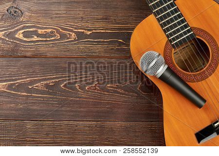 Acoustic Guitar With Microphone On Wooden Background. Classical Guitar With Microphone On Brown Wood