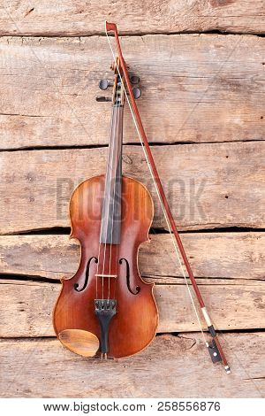 Violin And Fiddle Stick On Wooden Planks. Vintage Violin And Bow On Old Wooden Boards, Top View.