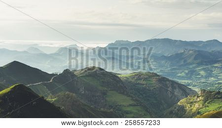 Morning Mist In The Mountain Peaks On Natural Landscape. Green Valley On Background Foggy Dramatic S