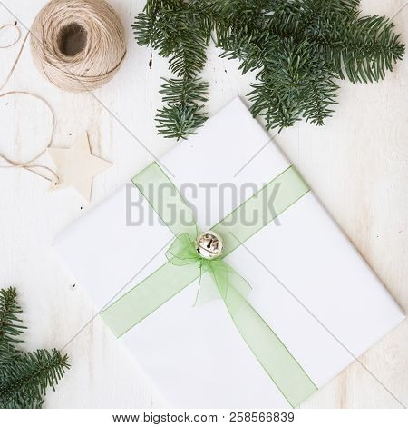Closeup Of Christmas Gift Decorated With Ribbon And Bell. New Year Present In White Paper On White W