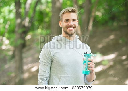 Athlete satisfied face hold bottle care hydration body after workout. Refreshing vitamin drink after great workout. Man athletic appearance holds water bottle. Athlete drink water after marathon. poster
