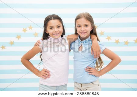 Happy childhood concept. Kids schoolgirls preteens happy together. Friendship from childhood. Girls smiling happy faces hug each other while stand striped background. Girls children best friends hugs. poster