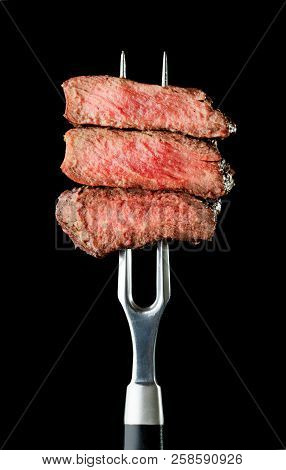 Grilled And Sliced Steak On Fork On Black Background