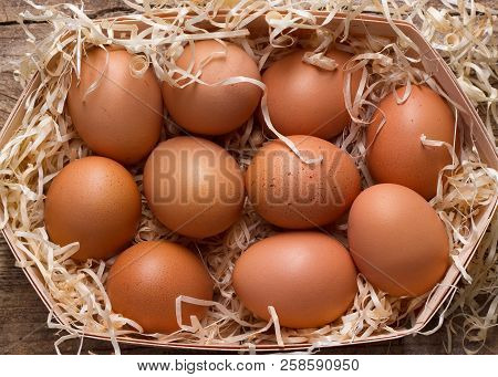Heap Of Eggs In Basket With Sawdust On Wooden Background