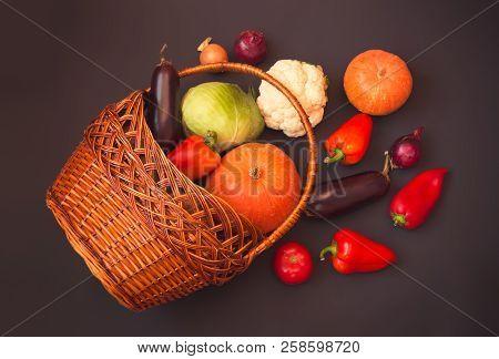Different Vegetables In Wicker Basket On Dark Background