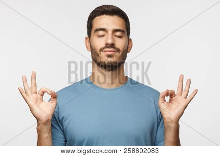Yoga and meditation concept. Concentrated relaxed man standing with closed eyes, having relaxation while meditating, trying to find balance and harmony isolated on gray poster
