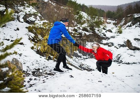 A Senior Couple Running Uphill In Snowy Winter Nature.