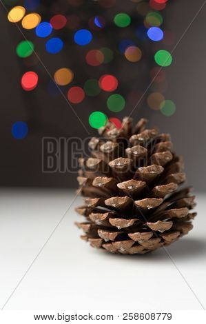 Round Conifer Cone With Defocused Colorful Christmas Tree Bokeh Lights. Vertical Orientation.