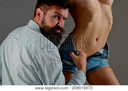 Stylish Bearded Man. Handsome Man With Nacked Woman On Gray Background. Portrait Of Sexy Brutal Man
