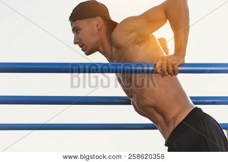 Side View Image Of Young Fitness Muscular Man Doing Exercises On Horizontal Crossbar Outdoors. Hands