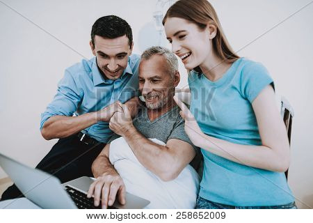 Support Family In Our Life. Technology In Our Life And Clinic. Man Help Old Man With Leptop In Hospi