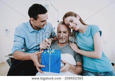 Gift For Old Man In Clinic. Young Family Give Old Man Gift. Happy Family. Good Mood In Family. Famil
