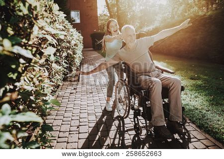 Aged And Girl. Body On Wheelchair. Therapy For Old Man In Stroller. Old Man And Young Girl Play. Fam