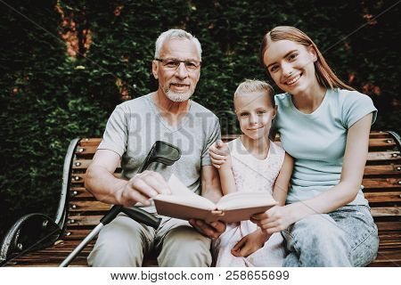 Old Man And With Family Sit On Bench. Smile Family With Good Old Man. Therapy For Aged. Rehabilitati