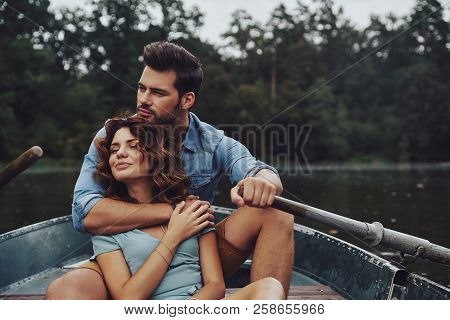 Loving Everything About Her. Beautiful Young Couple Embracing And Looking Away While Enjoying Romant