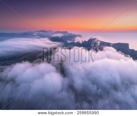 Aerial View Of Low Clouds, Mountains, Sea And Colorful Sky At Sunset. Above The Clouds At Dusk. Seas