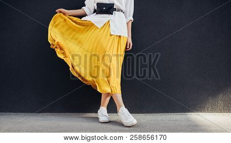 Cropped Body Shot Of Attractive Woman In Beautiful Yellow Skirt. Caucasian Female Fashion Model Stan