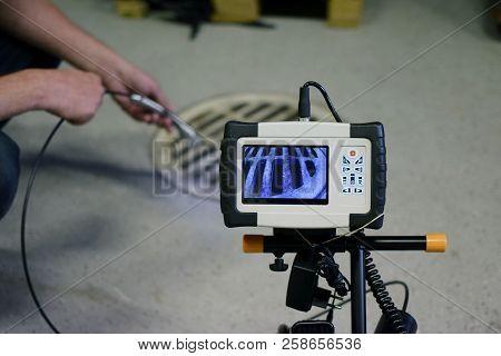 Man Start Using Sewer Inspection Camera. Horizontal Image.