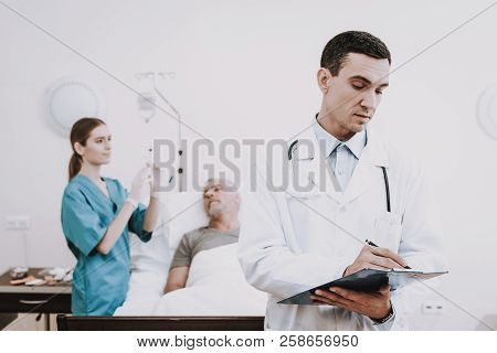 The Old Man Lies On A Cot In The Medical Ward. Next To Him Is A Doctor And A Nurse.the Doctor Interr