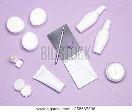 Various Cosmetic Products With Notebook And Pen On Women Table. Top View, Flat Lay. Beauty Shopping