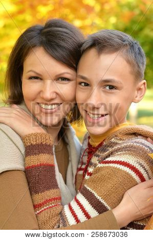 Close Up Portrait Of Mother With Son Hugging Outoors