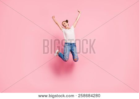 Full legs, body, size portrait of gril which is passing an exam, euphoric yung student jump up in white t-shirt and blue jeans isolated on vivid pink background poster