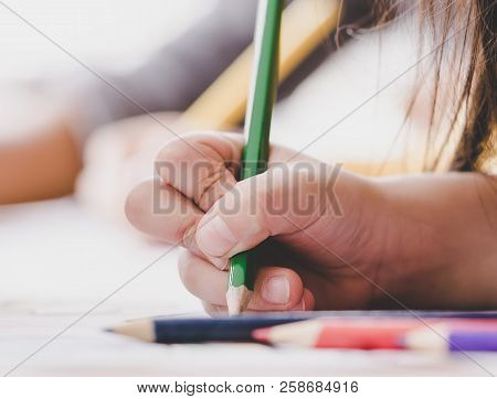 Child Hand Is Using Color Pencil To Practice Writing On A Paper.