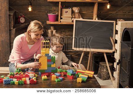 Mother And Happy Son Play With Constructor. Motherhood Concept. Nursery With Toys And Chalkboard On