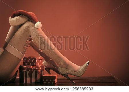 Christmas Legs Of Woman In Stocking And Shoes. New Year Legs On Red Background With Present. Santa C