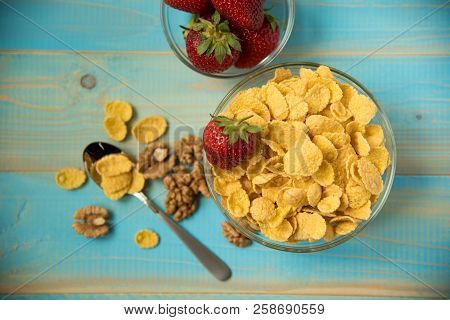 Tasty Cornflakes With Walnut And Strawberries In Glass Bowl