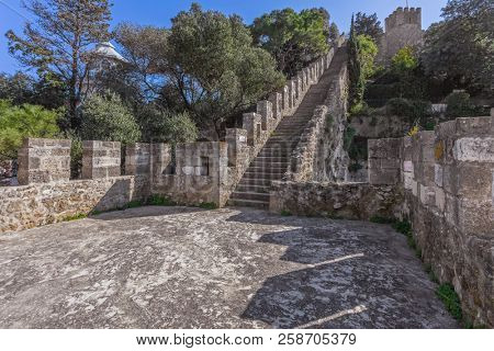 Lisbon, Portugal - February 1, 2017: Castelo de Sao Jorge aka Saint George Castle. Staircase on the Defensive walls with view of the wallwalk, battlements, ramparts, merlons and crenels in the towers
