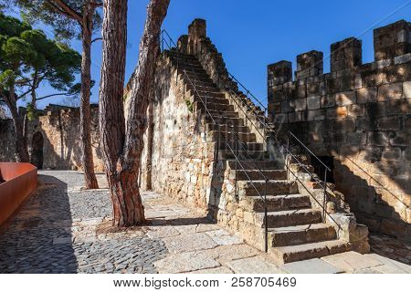 Lisbon, Portugal - February 1, 2017: Castelo de Sao Jorge aka Saint George Castle. Staircase in the defensive walls with a view of the wallwalk, battlements, ramparts, merlons and crenels