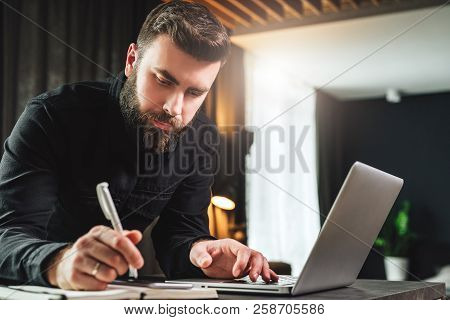Young Bearded Businessman In Black Shirt Is Standing By Computer, Making Notes In Notebook. Man Is W