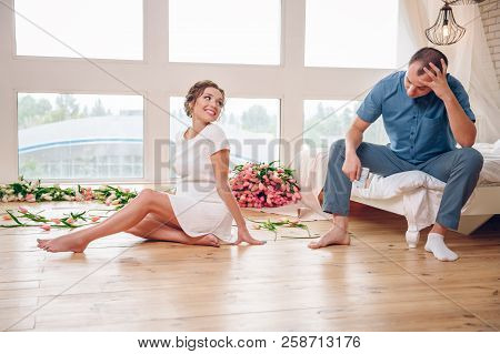 Happy Pregnant Woman With Her Husband Are Holding And Listening To Baby In Belly And Setting On Livi