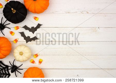 Halloween Side Border With Black, Orange And White Decor And Candy Over A White Wood Background. Top