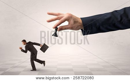 Small frail businessman with suitcase running away from big hand with chessman concept