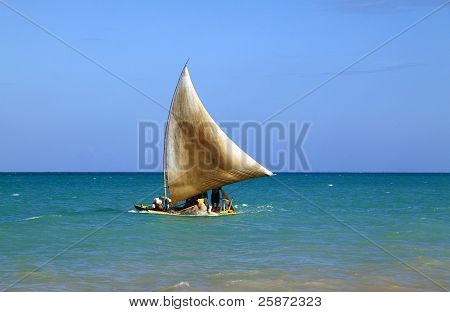 """Brazil Alagoas state Maceio Traditional """"jangada"""" fishing raft sailing on a turquoise Atlantic Ocean close to the shore of a tropical beach poster"""