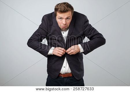 Fail In Business Concept. Young Untidy Man In Big Suit Trying To Fasten A Button. He Is Feeling Nerv