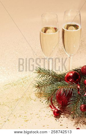 glasses of champagne, red shiny christmas balls and pine branch on glossing golden tabletop poster