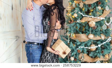 Beautiful Couple Is Kissing Near The New Year Tree. The Guy Gave A Christmas Gift To His Girlfriend