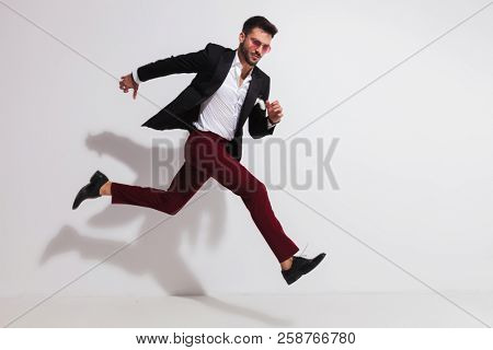 side view of attractive smart casual man jumping to side near a white wall, full length picture