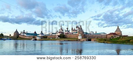 Panorama Of The Solovetsky Monastery With Blue Sea Bay In The Foreground At Sunset, Temples, Towers,