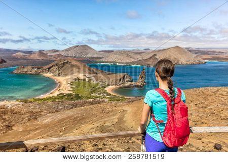 Galapagos islands cruise vacation tourist woman at Bartolome or Bartholomew island view on hiking shore excursion. Hiker Ecuador tourism.