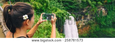 Hawaii travel tourism. Tourist woman taking pictures with mobile phone photo app of Wailua Falls waterfall on Kauai, Hawaii, USA.
