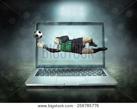 Caucassian soccer Player in dynamic action jump with ball in a professional sport game play on the laptop in football under stadium lights.