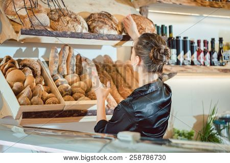 Shop assistant sorting bread to be sold in bakery shop