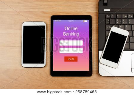 Digital Tablet With Online Banking On Screen With Smartphone And Laptop On Wooden Desk For Online Ba