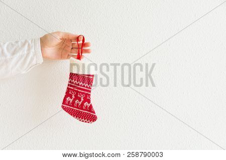 Young Caucasian Woman Holds In Hand Knitted Red Christmas Gift Stocking On White Wall Background. Fa