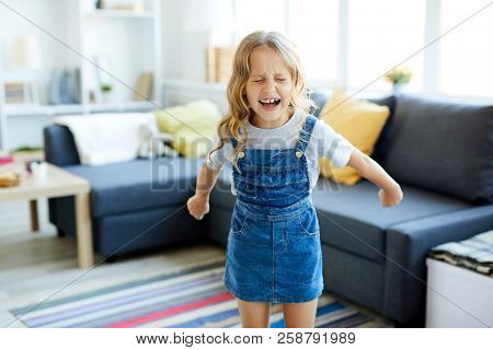 Little girl in casualwear screaming while standing in the center of living-room at home
