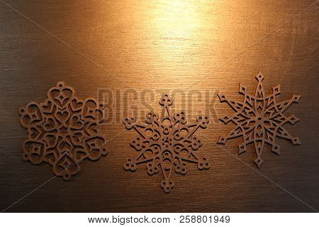 Golden Snowflake Ornaments On Golden Background. Laser Cut Christmas Decoration Wood Snowflakes On G